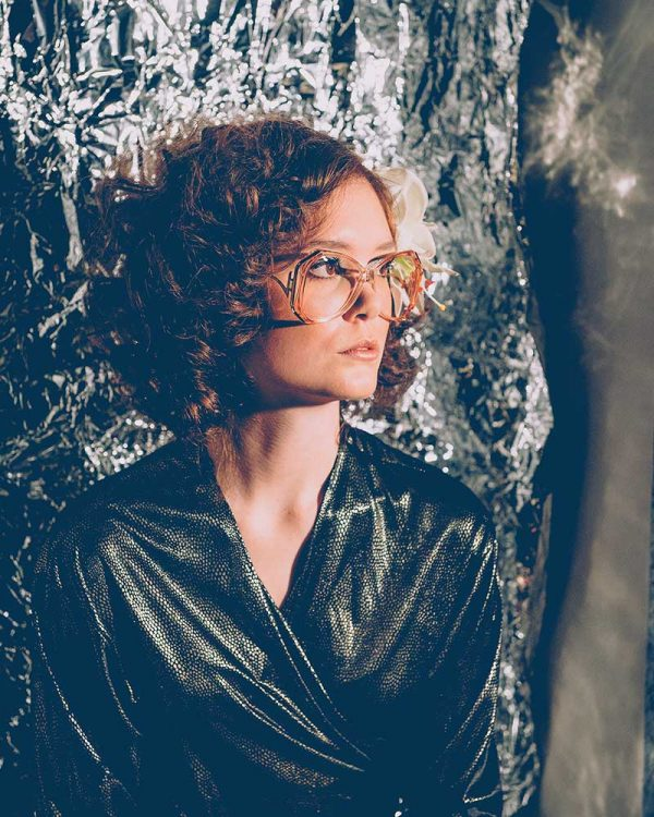 Kerry Curl - Image of a model wearing glasses and 70s clothing looking to the right of a 70s inspired space