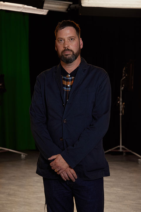 Liam Wells, Course Leader of BA Film and Moving Image Production at Norwich University of the Arts stands in the Sir John Hurt film studio.