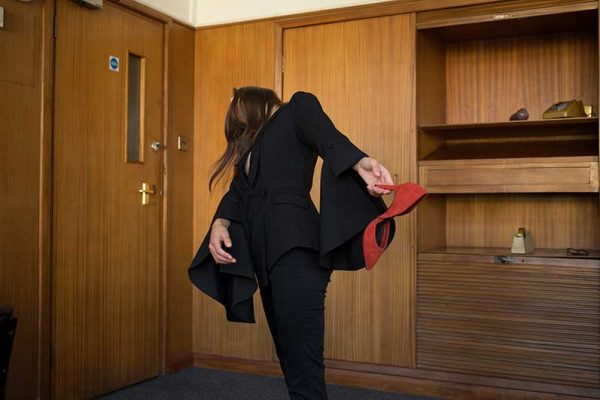 Olivia Harrould - Image of a female model standing in an office with her head tilted back and wearing a tailored red and black suit