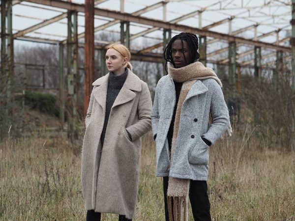Olivia Harrould - Image of two models standing in a field wearing winter jackets and staring off in the distance