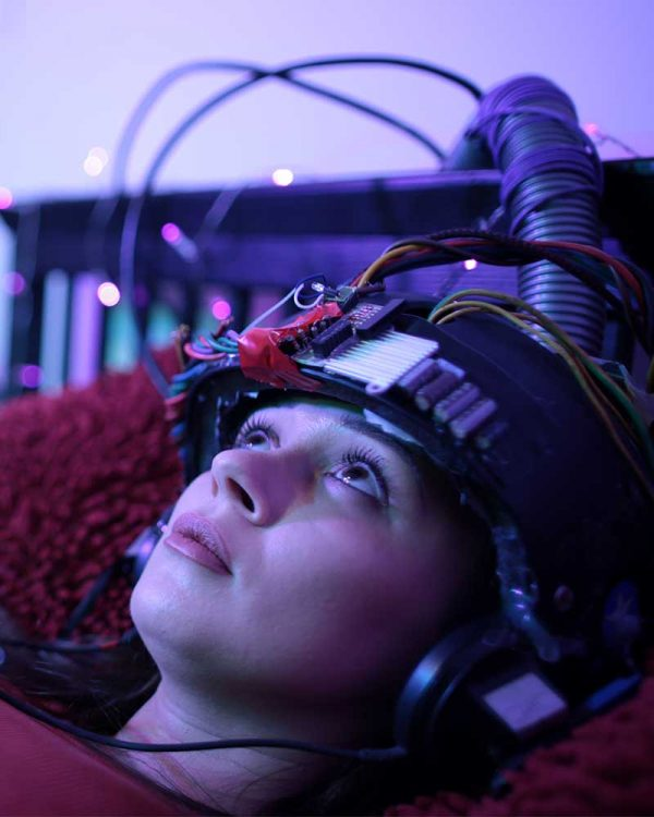 Luke Green - Still image of a girl laying on a bed, she has a helmet on which is connected to many wires and she is staring up at the ceiling