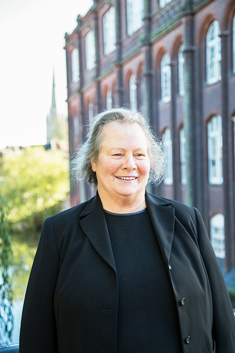 portrait photo of professor Lynda Morris standing in front of a river and smiling while looking away from camera with medium grey hair and a black suit jacket