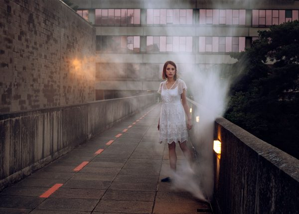 Gudbjorg Ylfa - Image of a model wearing a white dress standing in a urban landscape with smoke around her
