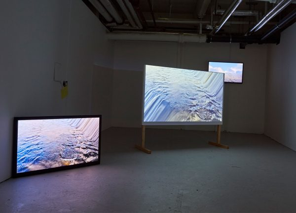 - Image of 3 screens in a gallery space with water on the screen