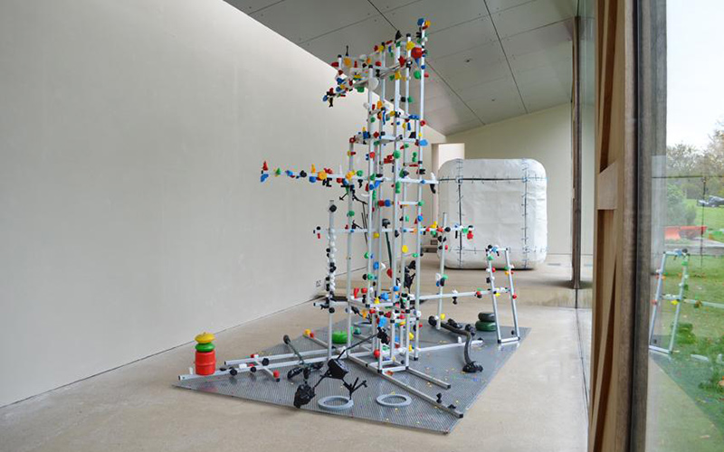 photo of white room with glass wall and a large metal frame structure covered in small primary colour objects with a large rounded cube in the back of the room
