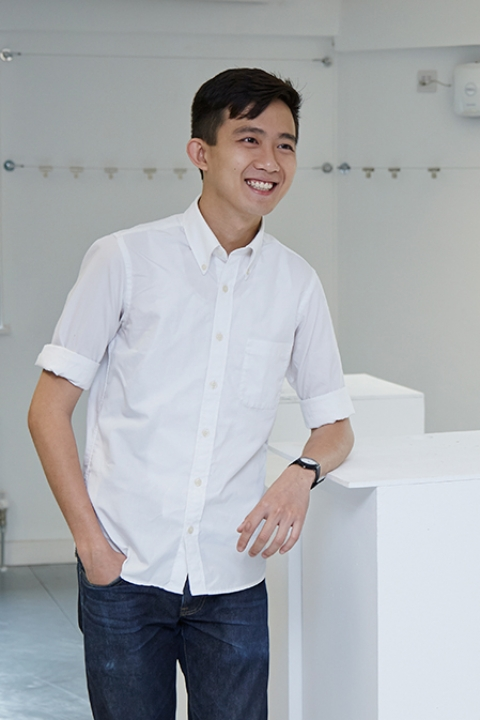 portrait photo of alum Mark Ng standing and leaning against a waist high table and smiling while looking away from camera with short swept black hair and a white shirt with rolled sleeves