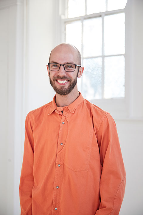 portrait photo of lecturer Matthew Benington standing with arms at side and smiling at camera with short brown hair with black square framed glasses and wearing an orange long sleeved loose shirt
