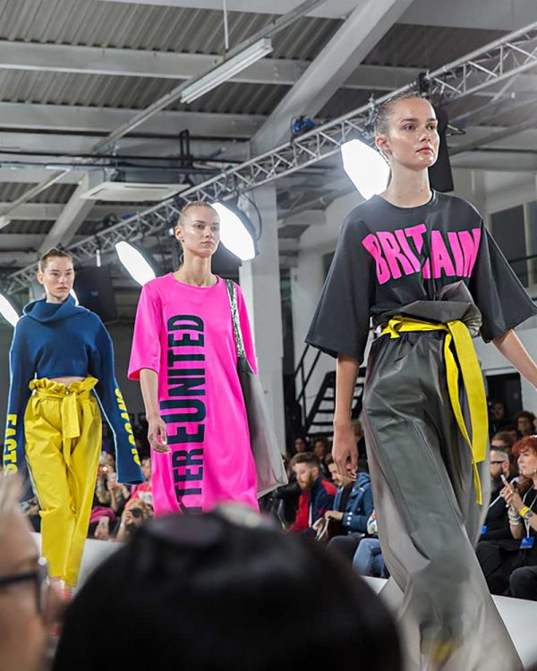Meg Tovey - Image of three models walking down a catwalk wearing clothes design by NUA Fashion student Meg Tovey