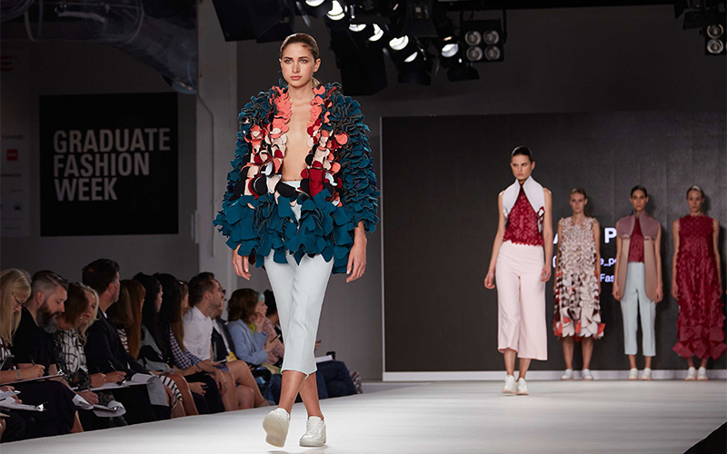 Photo of catwalk event with models walking down runway alongside audience with foreground model wearing a top of small curled fabric with deep blue on one side and pink on the other