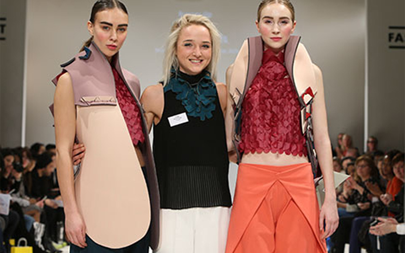 photo of graduate Alice Potts posing with models at a fashion catwalk event and smiling at camera with the models wearing neoprene materials crafted into jackets