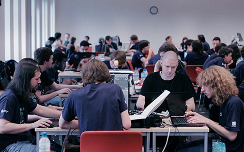 photo of entrants working around a desk for game jam competition Brains Eden with backdrop of several other tables with entrants working