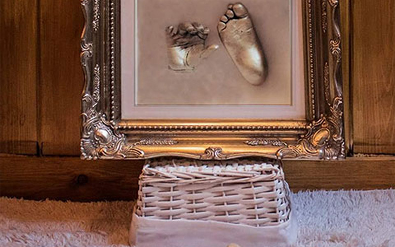 photo of room scenery with a framed casting of a small childs hand and foot on top of a wicker crate against a wooden wall