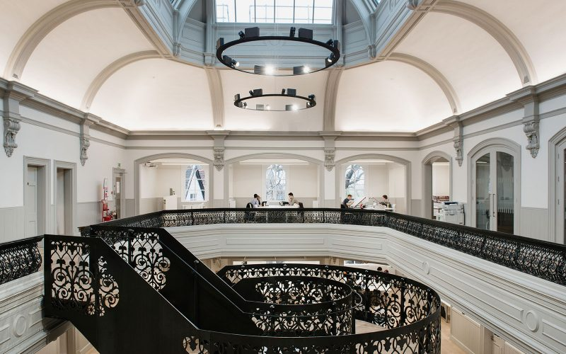 photo of NUA building boardman house shows large atrium with circular staircase in center with upper level wall with black metal railing and large white curved walls