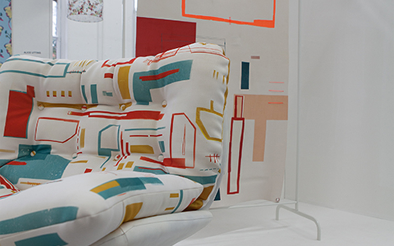 photo of Chalotte Eve Lindsey's final year print project of a large cushioned chair with quadrilateral shapes and connecting lines in pastel colours
