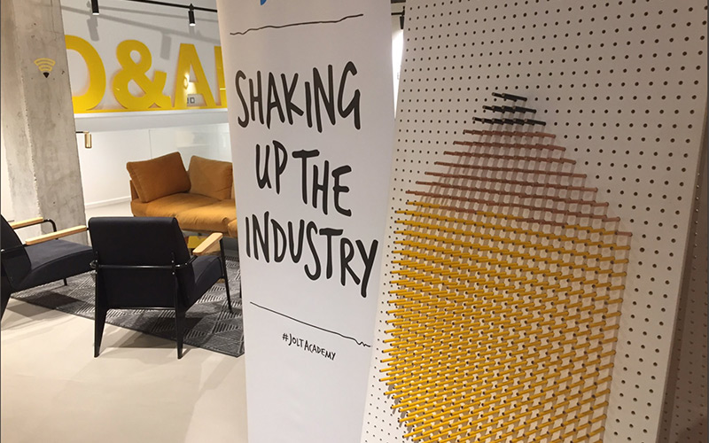 photo of D&AD industry event shows poster board close to camera with seating area in background