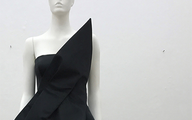 photo of mannequin wearing black strapless dress with a pointed front fold resting on the shoulder against a white blank wall