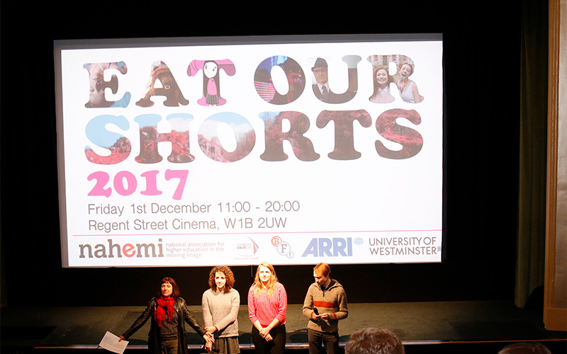 photo of screening at Eat Our Shorts 2017 shows organisers giving speech in front of stage with large projection of logo on a screen behind