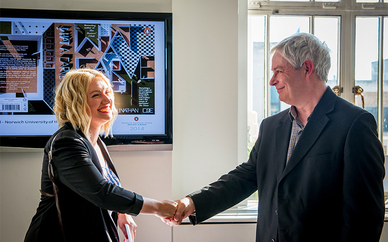 photo of Ellen Rockell shaking hands with Jonathan Coe in formal wear with a monitor in the background and a window