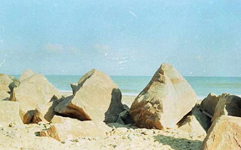 slightly faded photo of beach shows large sandy rocks positioned in front of the horizon with clear blue sky and an eerie stillness
