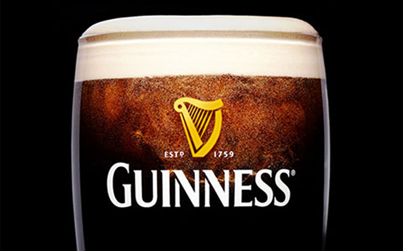 close up photo of a pint of guinness with fizz surrounding centre featuring label
