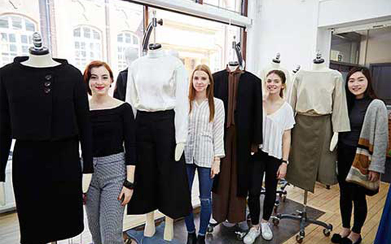 photo of NUA students standing next to mannequins with a variety of styles from long dakr and elegant to a wrapped top and skirt combination in light earth tones
