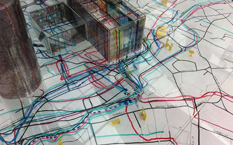 photo of landscape map with a mix of colourful lines drawn onto various routes and 3D models placed on the map