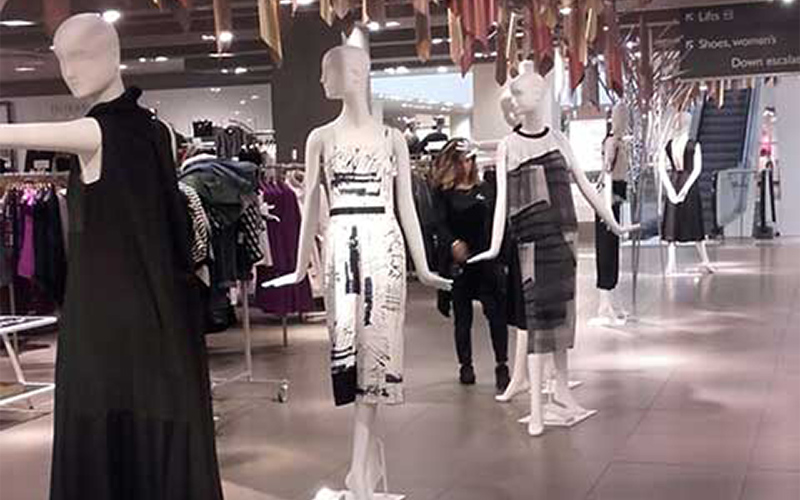 photo of mannequins inside of a shop and wearing a variety of dresses from black to metallic to greyscale printed fabric