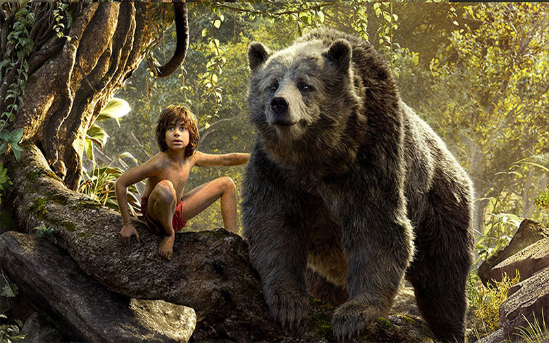 screenshot from The Jungle Book 2016 shows Mowgli and Baloo resting in a tree and observing something in the distance