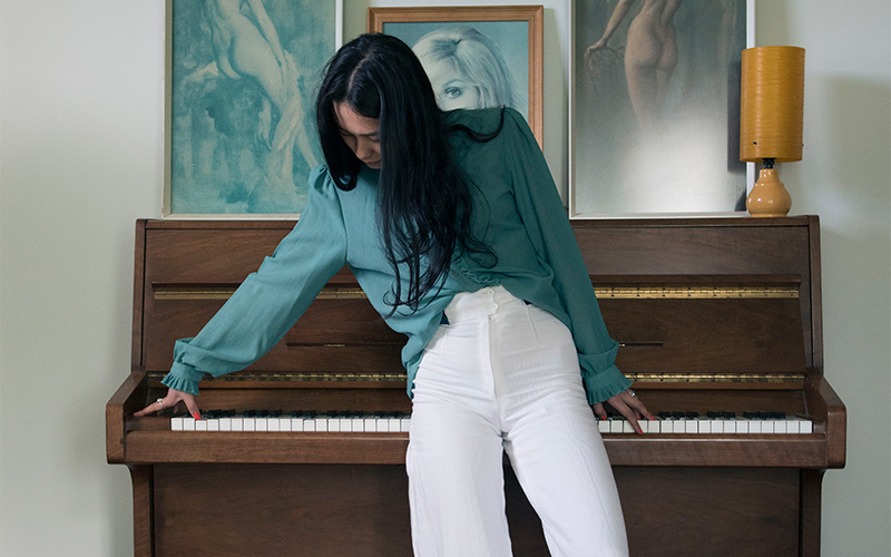 photo of model in white trousers and turquoise top leaning against a piano with arms outstretched