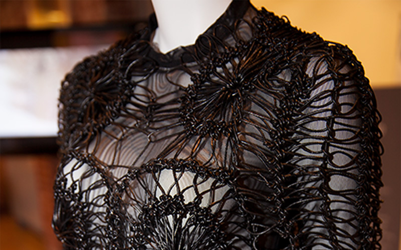 photo of thick black fibers woven into a dress in a complex pattern that follows the shape of the mannequin with a thin underlayer