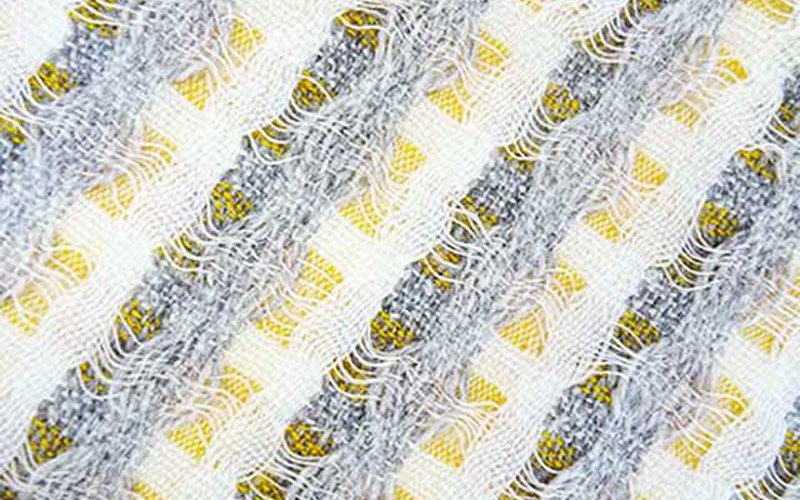 close up photo of Lizzie Kimbley's woven fabric shows interspaced gold and yellow colours with flat grey and white tones