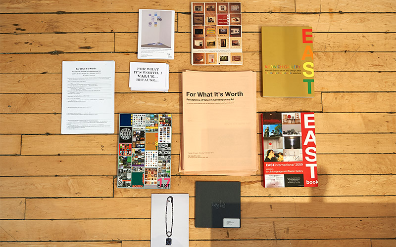 photo of exhibition documents for For What Its Worth exhibition curated by NUA students shows multiple brochures and handbooks laid out in loose grid pattern on wooden floor