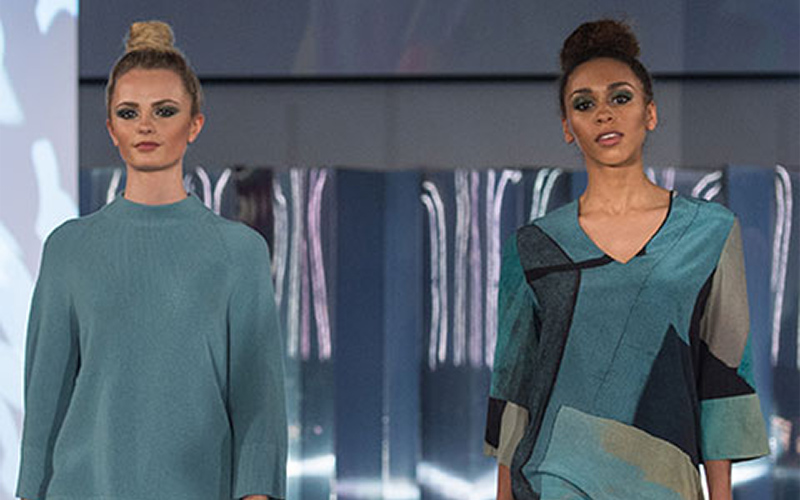 photo of Norwich Fashion Week catwalk show with two models, one wearing a long teal tall neck jumper and the other wearing an asymmetric patch fabric top with a v cut neck