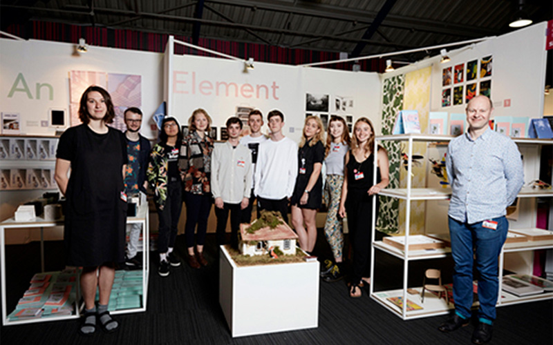 photo of students at New Designers stand surrounded by work such as models, books and illustrations