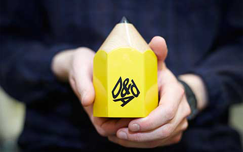photo of hands holding D&AD yellow pencil creative award with logo printed on the front