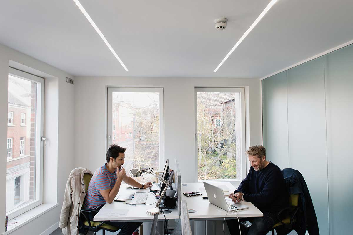 Men in agency doing work in front of computers