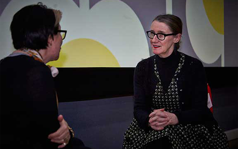 photo of designer Orla Kiely sitting on a chair and discussing her work
