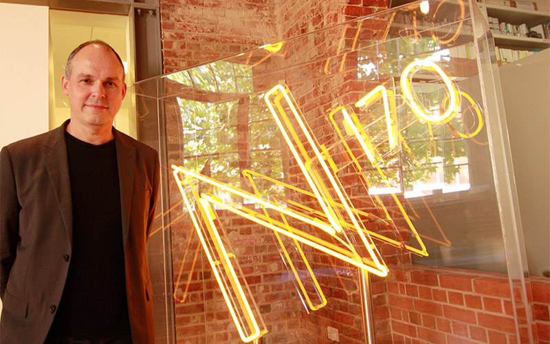 photo of Paul Franklin before a lecture to VFX students at NUA and standing next to a neon N170 sign
