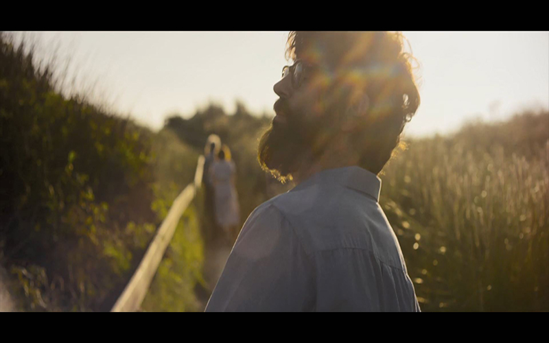 screenshot from Peter Middleton's film adaptation of Notes on Blindness shows bright lens flare with actor Dan Renton Skinner walking along country path and inspecting the surroundings
