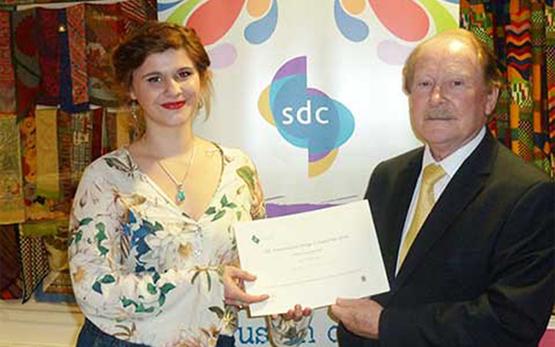NUA graduate Rosie Bulter-Hall poses with award from the Society of Dyers and Colourists in a floral top with an SDC banner behind