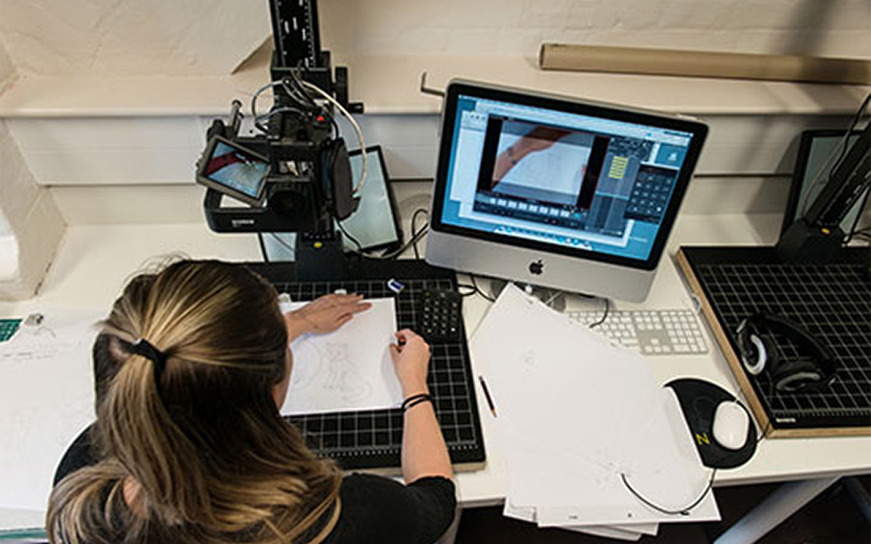 over the shoulder photo of student working at a rostrum studio with multiple animation frames on paper, a camera rig and a computer