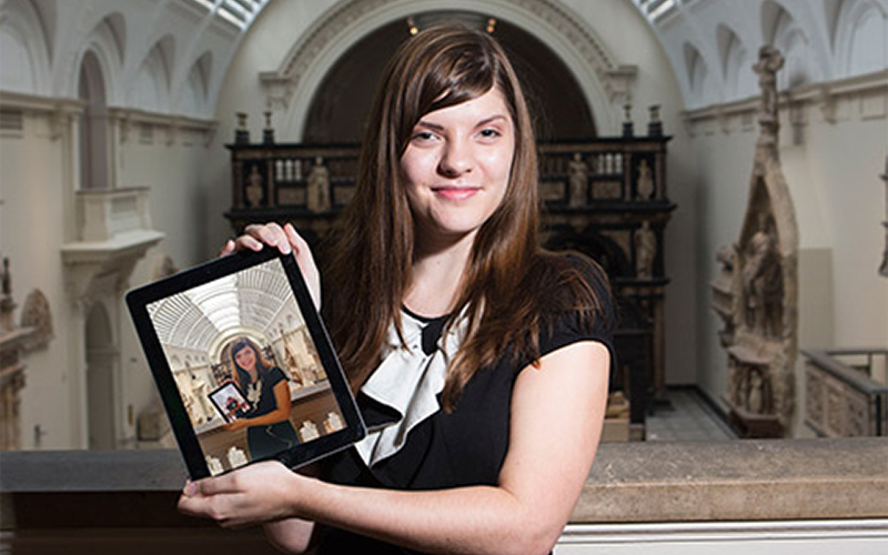 photo of Sophia George posing with an iPad in a black top with a gothic building interior in the background