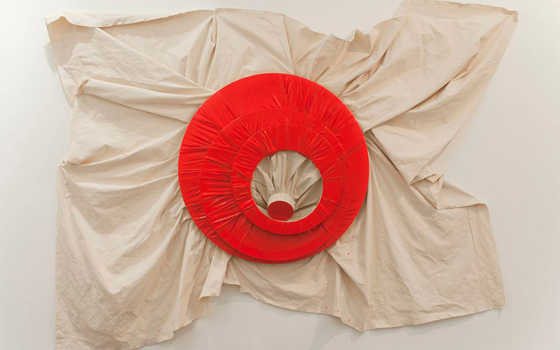photo of folded fabric pulled to a point in the centre with red fabric rings surrounding