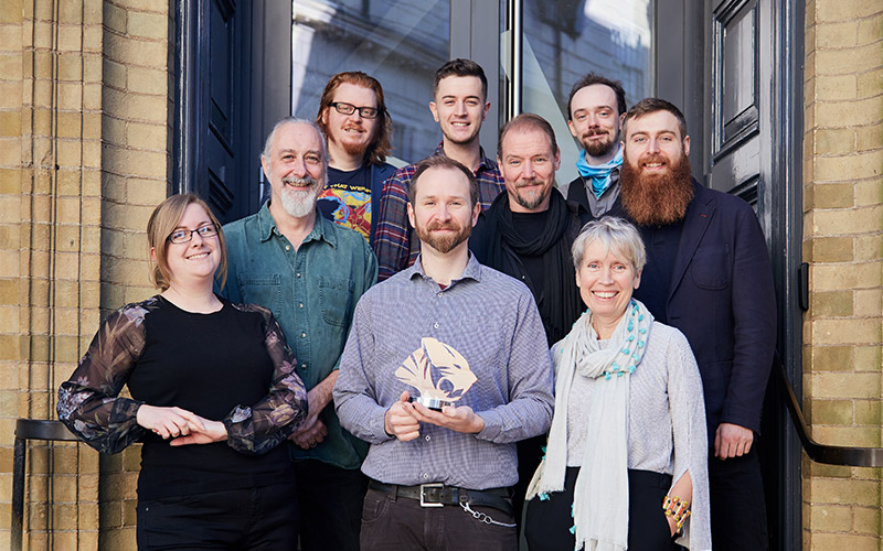 photo of NUA games art and design staff standing on steps holding the TIGA award for Best Educational Institution 2017