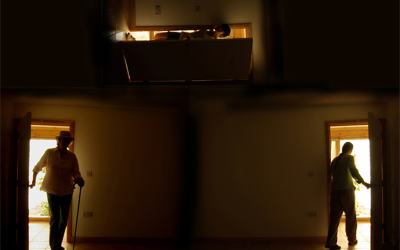 screenshot from Tony Hills' film The Doors shows a dark room with two doors to a bright outer area with someone entering on the left and someone leaving on the right with another sideways door above the room