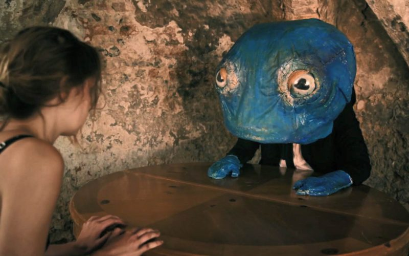 Screenshot from student film shows female actor in vest sitting across a table from a blue reptile puppet with bulbous eyes in corner of a grimy stone room