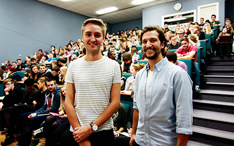 photo of NUA alum Miles Marshall and Matt Lurcock standing in front of NUA lecture theatre filled with students