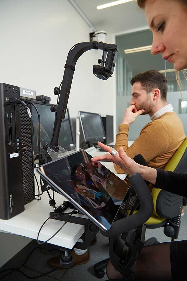 - photo of user experience lab at the NUA Ideas Factory shows a woman using an iPad with a tracking arm attached above and a man working at a desk in the background