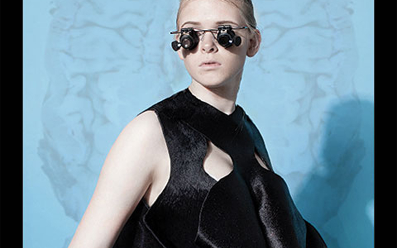 photo of model wearing velvet top with overlapping layered top and glasses consisting of small black lenses attached to a metal wire frame