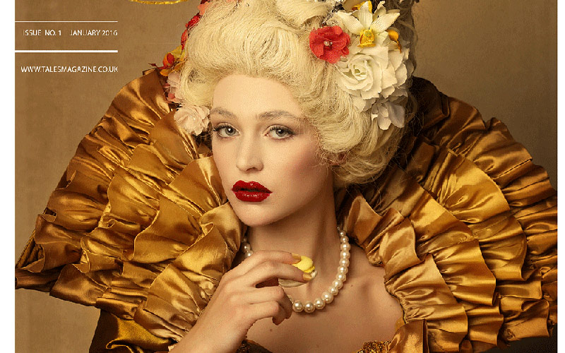 design shows model with deep red lips in extravagant gown with large frilled neckpiece and dress, large pearl necklace and blonde hair decorated with flowers